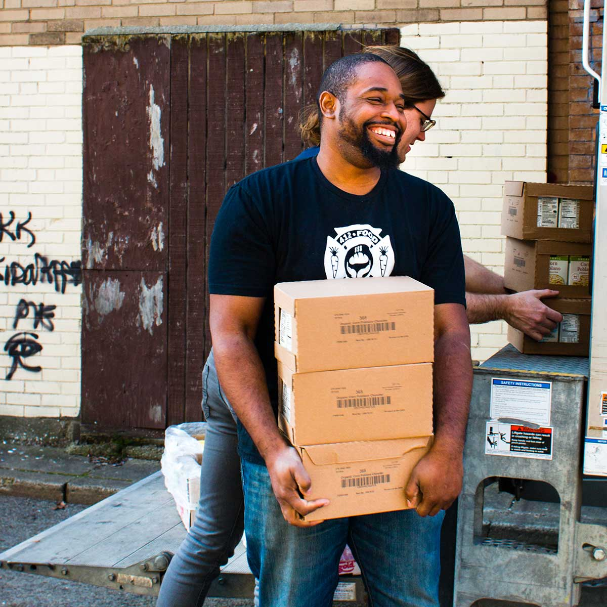 Man wearing a 412 Food Rescue t-shirt unloading boxes of rescued food.