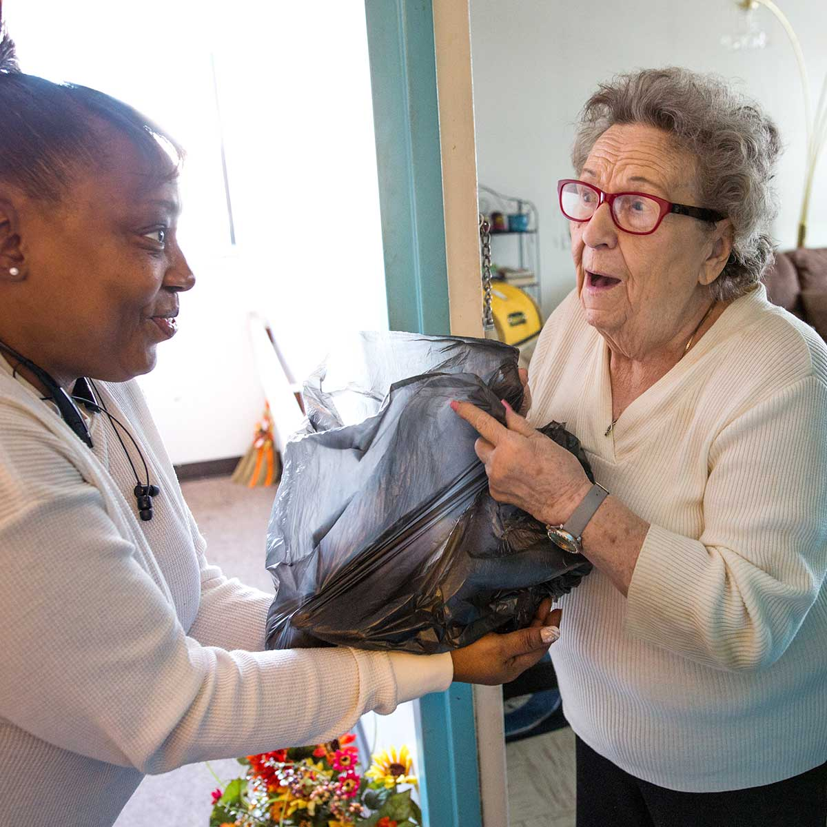 Woman delivering a grocery bag of food to an elderly woman
